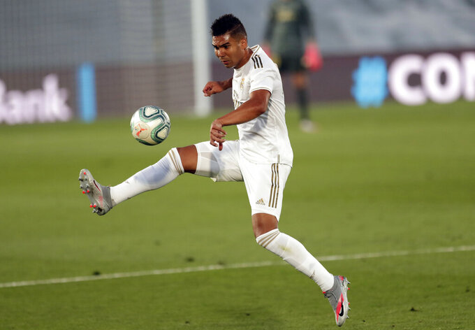 FILE - In this Thursday, July 16, 2020 file photo, Real Madrid's Casemiro, controls the ball during their Spanish La Liga soccer match against Villareal at the Alfredo di Stefano stadium in Madrid, Spain. Real Madrid players Eden Hazard and Casemiro have tested positive for COVID-19, the Spanish club said. The 29-year-old Belgium forward and the 28-year-old Brazil midfielder will now miss their trip to Valencia on Sunday, Nov. 8, 2020. (AP Photo/Bernat Armangue, file)