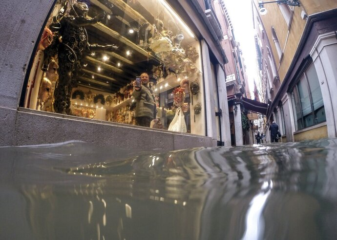 A man holds up a phone during a video call to show a a flooded alley outside a shop, in Venice, Italy, Friday, Nov. 15, 2019. Exceptionally high tidal waters returned to Venice on Friday, prompting the mayor to close the iconic St. Mark's Square and call for donations to repair the Italian lagoon city just three days after it experienced its worst flooding in 50 years. (AP Photo/Luca Bruno)