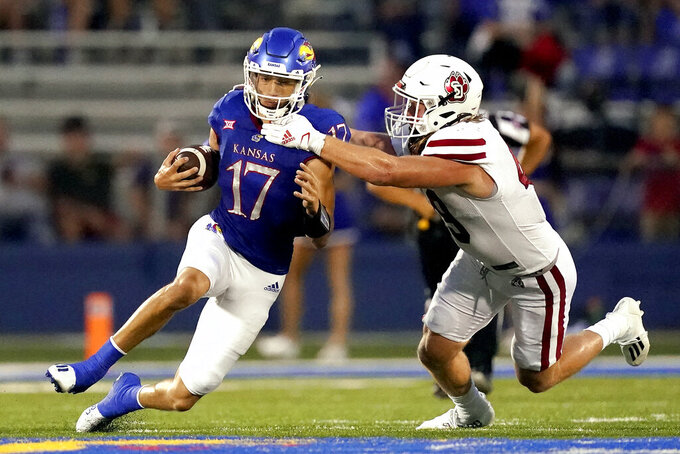 Kansas quarterback Jason Bean (17) is tackled by South Dakota linebacker Brock Mogensen (49) during the first half of an NCAA college football game Friday, Sept. 3, 2021, in Lawrence, Kan. (AP Photo/Charlie Riedel)