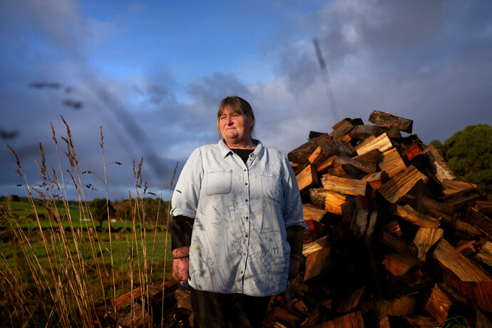 Carmall Casey stands for a portrait in her yard in Black River, Tasmania, Australia, Wednesday, July 24, 2019. From her home in rural northwest Tasmania, not far from the poppy fields that produce half the world's supply of the raw ingredients in pharmaceutical opiates, Casey seethes over a system she says pushed her and so many others into addiction. It is a system that has made opioids the cheap and easy alternative for so many Australians. (AP Photo/David Goldman)