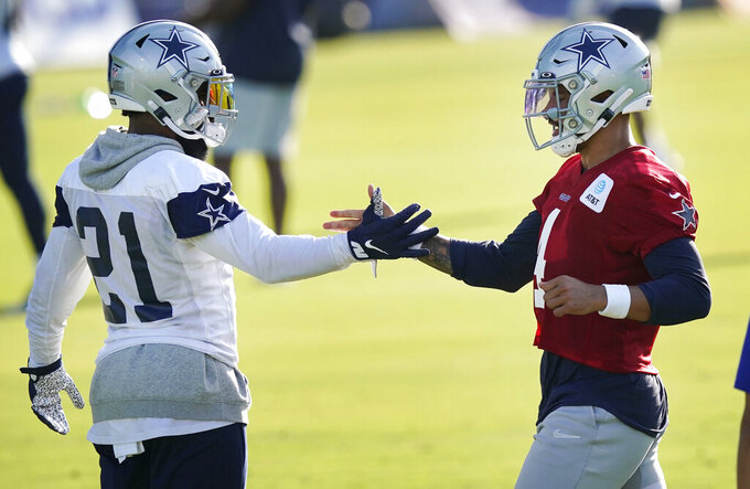 Dallas Cowboys quarterback Dak Prescott (4) greets teammate running back Ezekiel Elliott (21) at the beginning of an NFL football training camp practice in Frisco, Texas, Friday, Aug. 14, 2020. (AP Photo/LM Otero)