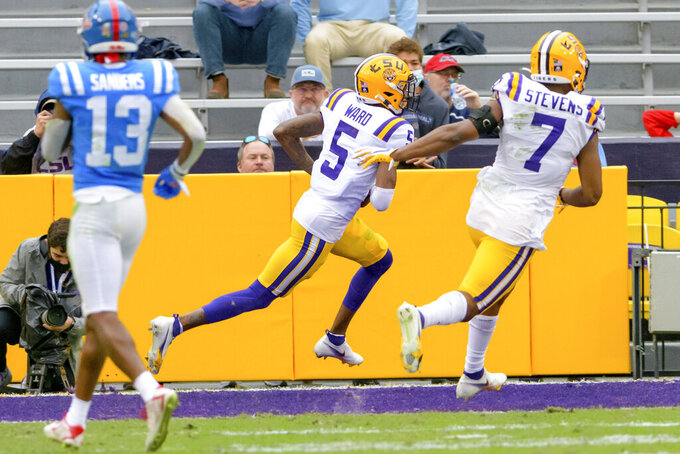 LSU cornerback Jay Ward (5) celebrates after scoring a touchdown after intercepting a ball intended for Mississippi wide receiver Braylon Sanders (13) during the first half of an NCAA college football game in Baton Rouge, La., Saturday, Dec. 19, 2020. (AP Photo/Matthew Hinton)