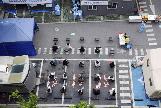 People wait to take a test for coronavirus at a testing facility of health center in Seoul, South Korea, Tuesday, May 12, 2020. As South Korea grapples with a new spike in coronavirus infections thought to be linked to nightspots in Seoul, including several popular with gay men, it's also seeing rising homophobia that's making it difficult for sexual minorities to come forward for diagnostic tests. (Choi Jae-gu/Yonhap via AP)