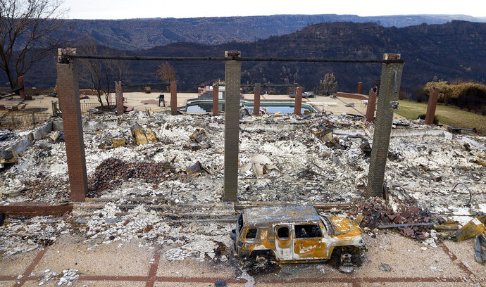 FILE - In this Dec. 3, 2018, file photo, a vehicle rests in front of a home leveled by the Camp Fire in Paradise, Calif. A grand jury investigation into the 2018 wildfire that killed 85 people in Northern California, wiping out a town, found that Pacific Gas & Electric repeatedly ignored warnings about its failing power lines in the area, performed inadequate inspections and ignored pleas from employees about deteriorating equipment. (AP Photo/Noah Berger, File)