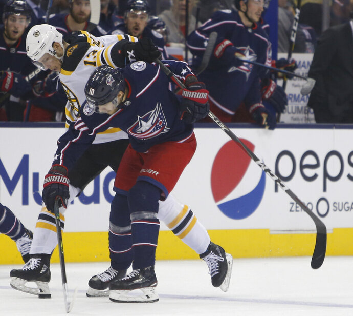 Boston Bruins' Charlie Coyle, left, and Columbus Blue Jackets' Alexander Wennberg, of Sweden, fight for a loose puck during the second period of Game 3 of an NHL hockey second-round playoff series Tuesday, April 30, 2019, in Columbus, Ohio. (AP Photo/Jay LaPrete)