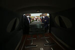 FILE - In this April 18, 2020, file photo, Mortician Cordarial O. Holloway, foreground left, funeral director Robert L. Albritten, foreground right, and funeral attendants Eddie Keith, background left, and Ronald Costello place a casket into a hearse in Dawson, Ga. America's failure so far to contain the spread of the coronavirus as it moves across the country has been met with astonishment and alarm on both sides of the Atlantic. (AP Photo/Brynn Anderson, File)