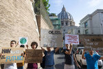 Activists hold up signs outside the Vatican as Pope Francis meets with oil executives, Friday, June 14, 2019. The meeting marked the second year that Francis has invited oil and financial sector executives to the Vatican to impress upon them his concern that preserving God's creation is one of the fundamental challenges facing humankind today. Signs in Italian read