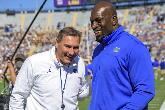 Florida head coach Dan Mullen talks with WWE Superstar Titus O'Neil, who previously played for the University of Florida with his given name of Thaddeus Bullard, Sr., before an NCAA college football game against LSU in Baton Rouge, La., Saturday, Oct. 16, 2021. (AP Photo/Matthew Hinton)