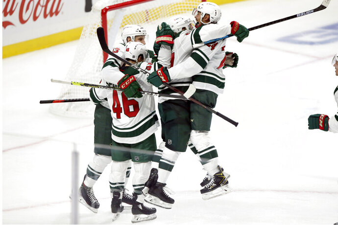Minnesota Wild defenseman Mathew Dumba, right, leaps into the arms of left wing Kirill Kaprizov, second from right, after an overtime goal against the Los Angeles Kings, as Jared Spurgeon (46) and Nick Bonino, left, join the celebration at an NHL hockey game in Los Angeles, Thursday, Jan. 14, 2021. (AP Photo/Alex Gallardo)