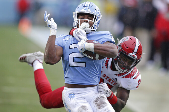 North Carolina State's Jarius Morehead reaches around North Carolina's Jordon Brown (2) during the first half of an NCAA college football game in Chapel Hill, N.C., Saturday, Nov. 24, 2018. (AP Photo/Gerry Broome)