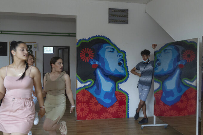 """From left, Dijana Ferhatovic, 18, Silvia Sinani, 24, and Zlata Ristic, 27, members of the Pretty Loud band, practice at a music studio in Belgrade, Serbia, Wednesday, June 16, 2021. A female Roma, or Gypsy, band in Serbia has used music to preach women's empowerment within their community. Formed in 2014, """"Pretty Loud"""" symbolically seeks to give a louder voice to Roma girls, encourage education and steer them away from the widespread custom of early marriage. (AP Photo/Marko Drobnjakovic)"""