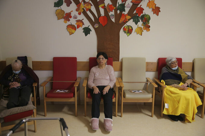 Residents sit at a distance from each other in the television room of the care home where they live, in Amadora, outside Lisbon, Friday, Dec. 11, 2020. As a resurgence of the pandemic in the fall looked set to overwhelm Portuguese care homes, and the country's public health service struggled to cope, the government mobilized all the resources it could. That included deploying military units. (AP Photo/Armando Franca)