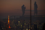 Silhouetted against the warm sunset skyline and the illuminated Tokyo Tower, visitors are reflected on the glass walls of a rooftop observation deck Thursday, Jan. 21, 2021, in Tokyo. (AP Photo/Kiichiro Sato)