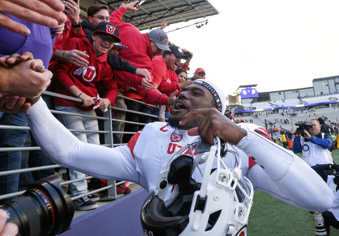 Utah quarterback Tyler Huntley celebrates with fans after after an NCAA college football game against Washington, on Saturday, Nov. 2, 2019, in Seattle. Utah won 33-28. (AP Photo/Stephen Brashear)