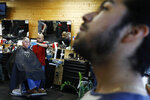 John Paul Garcia, 20, right, waits for his turn at the barber shop, Blast Barber Studio/Barberia, in Burlington, N.C., Thursday, March 12, 2020. (AP Photo/Jacquelyn Martin)