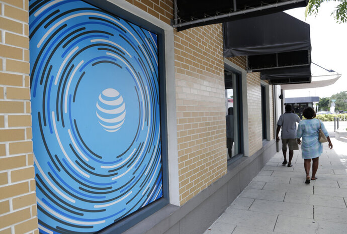 In this Thursday, July 18, 2019 photo, people walk by an AT&T retail store in Miami. Shares in AT&T have been mostly flat since April, when the second-largest wireless carrier after Verizon said it had lost almost 630,000 video customers in the first quarter. Analysts expect its profit slipped in the second quarter, even as revenue increased. AT&T reports quarterly results on Wednesday, July 24. (AP Photo/Lynne Sladky)