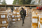 A police officer keeps guard over electoral materials still stacked in boxes at the offices of the Independent National Electoral Commission in Kano, in northern Nigeria, Saturday, Feb. 16, 2019. Nigeria's electoral commission delayed the presidential election until Feb. 23, making the announcement a mere five hours before polls were set to open Saturday. (AP Photo/Ben Curtis)