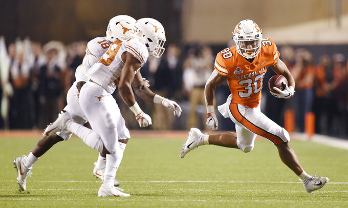 Oklahoma State running back Chuba Hubbard, right, runs down field under pressure from Texas defensive backs Davante Davis, left back, and Josh Thompson in the first half of an NCAA college football game in Stillwater, Okla., Saturday, Oct. 27, 2018. (AP Photo/Brody Schmidt)