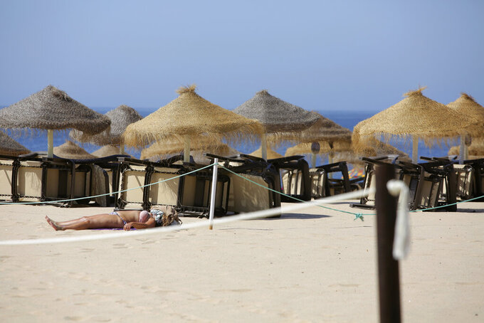 A woman sunbathes next to overturned deck chairs and sunshades at the beach in Oeiras, outside Lisbon, Wednesday, July 15, 2020. Temperatures are rising in Portugal, with weather authorities expecting to declare it a heatwave later this week. (AP Photo/Armando Franca)