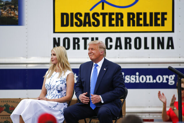 President Donald Trump, right, sits with his daughter Ivanka Trump during and event about the