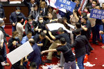 """In this image made from video, lawmakers fight during a parliament session in Taipei, Taiwan, Friday, Nov. 27, 2020. Taiwan's lawmakers got into a fist fight and threw pig guts at each other Friday over a soon-to-be enacted policy that would allow imports of U.S. pork and beef. The banner at center top reads: """"Protest against ractopamine pork, We want a referendum."""" (FTV via AP)"""