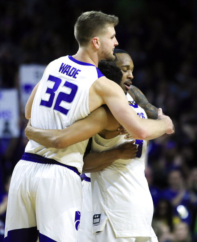 Kansas State seniors Dean Wade (32), Barry Brown Jr., back, and Kamau Stokes, middle, hug as they are replaced during the second half of an NCAA college basketball game against Oklahoma in Manhattan, Kan., Saturday, March 9, 2019. Kansas State defeated Oklahoma 68-53. (AP Photo/Orlin Wagner)