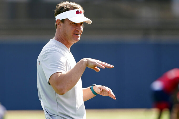 FILE - In this Aug. 9, 2021 file photo, Mississippi NCAA college football coach Lane Kiffin gestures towards his players during practice in Oxford, Miss.  Kiffin will miss the opener against Louisville with a breakthrough case of COVID-19. Kiffin announced the positive test on Saturday, Sept. 4, two days ahead of the Rebels' opener in Atlanta. Kiffin, his staff and his players are all fully vaccinated. He said no other members of the team are expected to miss the game because of COVID-19.(AP Photo/Rogelio V. Solis, File)