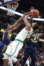 Boston Celtics guard Brad Wanamaker (9) shoots between Indiana Pacers center Myles Turner (33) and guard Aaron Holiday (3) during the second half of an NBA basketball game in Indianapolis, Wednesday, Dec. 11, 2019. The Pacers defeated the Celtics 122-117. (AP Photo/Michael Conroy)