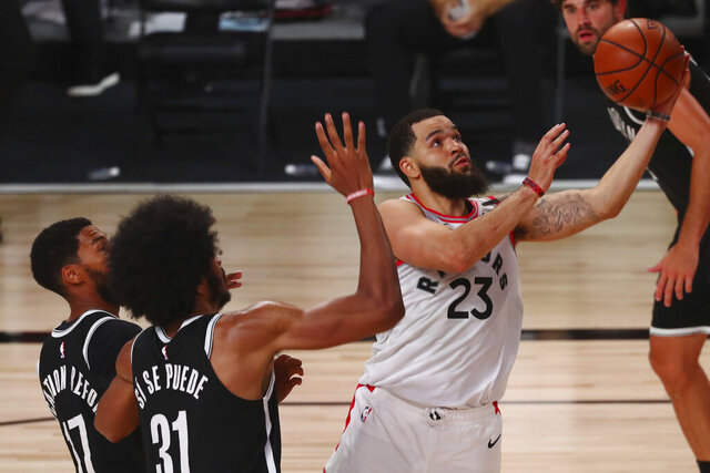 Toronto Raptors guard Fred VanVleet (23) goes up to shoot past Brooklyn Nets center Jarrett Allen (31) and guard Garrett Temple (17) during the second half of Game 1 of an NBA basketball first-round playoff series, Monday, Aug. 17, 2020, in Lake Buena Vista, Fla. (Kim Klement/Pool Photo via AP)