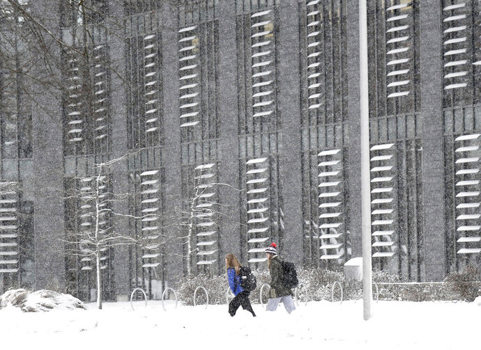 Wheaton College students make their way to the Science and Technology building on the Norton, Mass. campus Tuesday, Dec. 3, 2019 after the area received several inches of new snow overnight. (Mark Stockwell/The Sun Chronicle via AP)