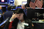 Trader Phyllis Arena Woods works on the floor of the New York Stock Exchange, Friday, Feb. 8, 2019. Stocks are opening lower on Wall Street as a mixed bag of earnings reports didn't inspire investors to get back to buying stocks. (AP Photo/Richard Drew)