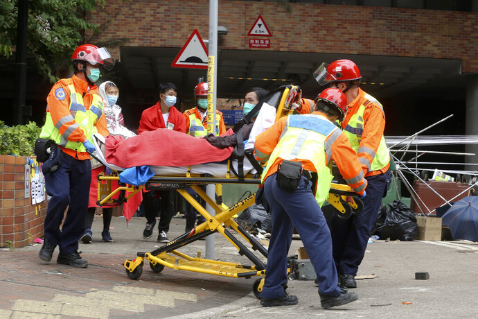 Medical workers transport an injured protester on a stretcher at Hong Kong Polytechnic University in Hong Kong, Tuesday, Nov. 19, 2019. About 100 anti-government protesters remained holed up at the university Tuesday as a police siege of the campus entered its third day. (AP Photo/Achmad Ibrahim)
