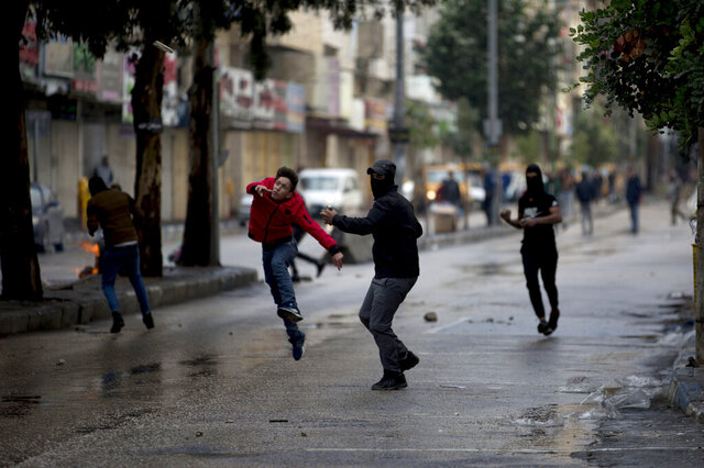 A Palestinian demonstrator hurls stones at Israeli troops during a protest in the West Bank city of Hebron, Monday, Dec. 9, 2019. Palestinian residents held a general strike to protest an Israeli plan to build a new Jewish neighborhood in the heart of the West Bank's largest city.  (AP Photo/Majdi Mohammed)