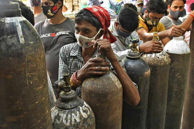 Indians wait to refill oxygen cylinders for COVID-19 patients at a gas supplier facility in New Delhi, India, Saturday, May 8, 2021. Infections have swelled in India since February in a disastrous turn blamed on more contagious variants as well as government decisions to allow massive crowds to gather for religious festivals and political rallies. (AP Photo/Ishant Chauhan)