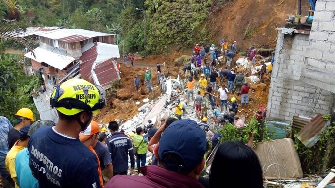 In this handout photo released by the Caldas Department Press Office, rescue workers attend to the wreckage of a house destroyed by a landslide in Marquetalia, Colombia, Thursday, Oct. 11, 2018. At least 12 people were killed in a landslide triggered by heavy rains in a neighborhood of the municipality of Marquetalia in northwest Colombia, said the National Unit for Disaster Risk Management. (Caldas Department Press Office via AP)