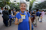 """In this Feb. 19. 2019 photo, Alesia Santacroce, a volunteer shows her credential during a meeting for recruiting volunteers, at a square in Caracas, Venezuela. Opposition leader Juan Guaido, who has declared himself Venezuela's interim-president to overthrow Maduro, has called on """"caravans"""" of volunteers to deliver the supplies to the neediest Venezuelans. (AP Photo/Fernando Llano)"""