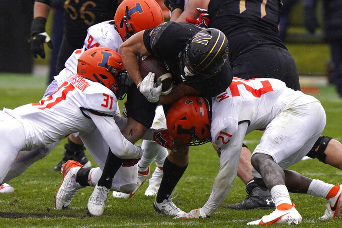 Northwestern running back Evan Hull, center, is tackled by Illinois defenders during the second half of an NCAA college football game in Evanston, Ill., Saturday, Dec. 12, 2020. Northwestern won 28-10. (AP Photo/Nam Y. Huh)