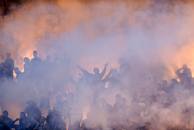 FILE - In this Thursday, May 23, 2019 file photo, Partizan Belgrade fans light flares and smoke bombs as they cheer on their team on during the Serbian Cup Final soccer fixture against Red Star Belgrade in Belgrade, Serbia. Red Star Belgrade can host the biggest crowd for a game in Europe since soccer's shutdown in the pandemic ended last month when the Serbian title winner completes its season on June 20, 2020. Another big crowd is expected Wednesday June 10, 2020 in a passionate atmosphere now rarely seen in Europe. Partizan hosts city rival Red Star in the domestic cup semi-finals at its 30,000-capacity home. (AP Photo/Marko Drobnjakovic, File)