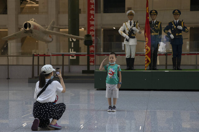 A child salutes for a photo near statues of Chinese military honor guards at the military museum in Beijing on Thursday, Sept. 3, 2020. Seventy-five years after Japan's surrender in World War II, and 30 years after its economic bubble popped, the emergence of a 21st century Asian power is shaking up the status quo. As Japan did, China is butting heads with the established Western powers, which increasingly see its growing economic and military prowess as a threat. (AP Photo/Ng Han Guan)
