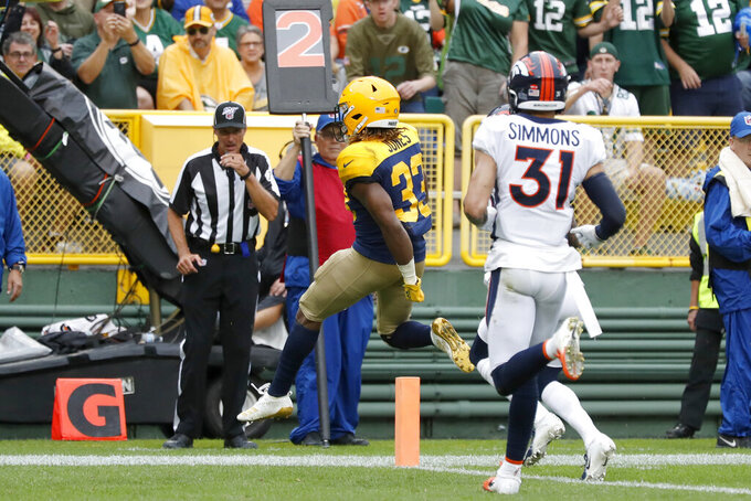 Green Bay Packers running back Aaron Jones (33) scores past Denver Broncos free safety Justin Simmons (31) during the second half of an NFL football game Sunday, Sept. 22, 2019, in Green Bay, Wis. (AP Photo/Matt Ludtke)