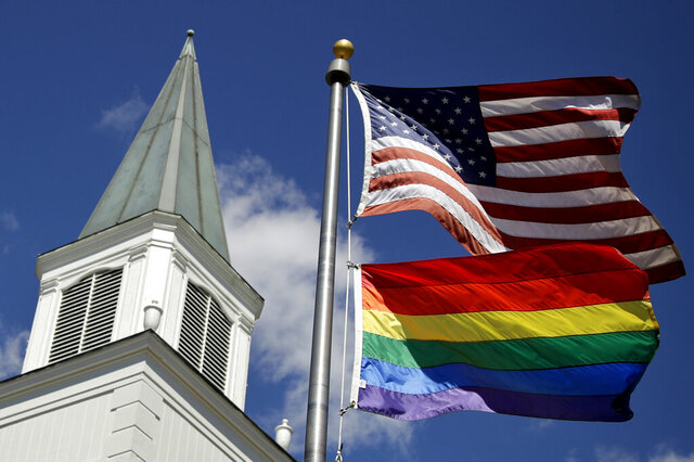 FILE - In this April 19, 2019 file photo, a gay pride rainbow flag flies along with the U.S. flag in front of the Asbury United Methodist Church in Prairie Village, Kan. Had there been no COVID-19 coronavirus pandemic, America's largest mainline Protestant denomination would be convening in May 2020 for a likely vote on breaking up over differences on same-sex marriage and ordination of LGBTQ pastors. (AP Photo/Charlie Riedel, File)
