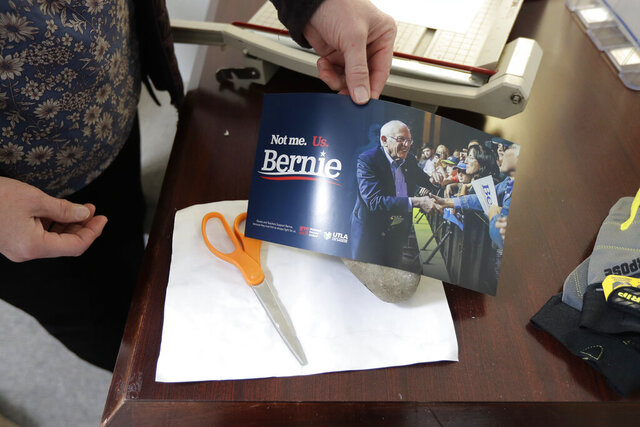 Carin Chase, director of Washington state for the campaign of Democratic presidential candidate Sen. Bernie Sanders, I-Vt., uses a Sanders campaign sign to cover a rock Saturday, Feb. 22, 2020, in Seattle that was used to break the glass of the door to Sanders' Seattle headquarters Friday night as she makes a humorous reference to a