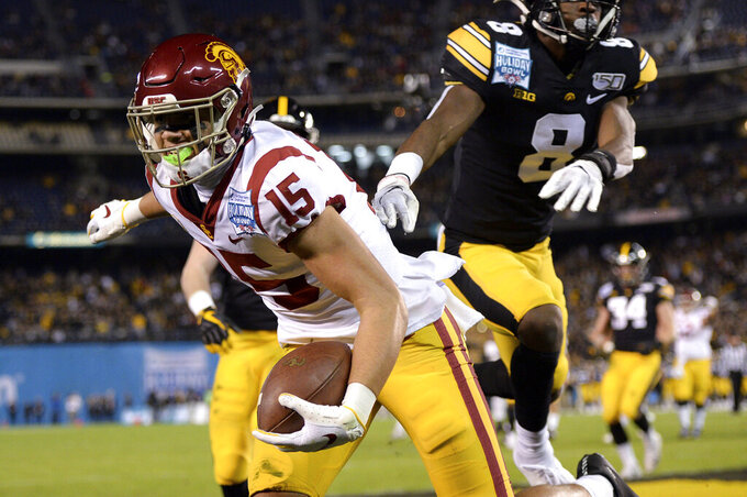 Southern California wide receiver Drake London (15) scores a touchdown ahead of Iowa defensive back Matt Hankins (8) during the first half of the Holiday Bowl NCAA college football game Friday, Dec. 27, 2019, in San Diego. (AP Photo/Orlando Ramirez)