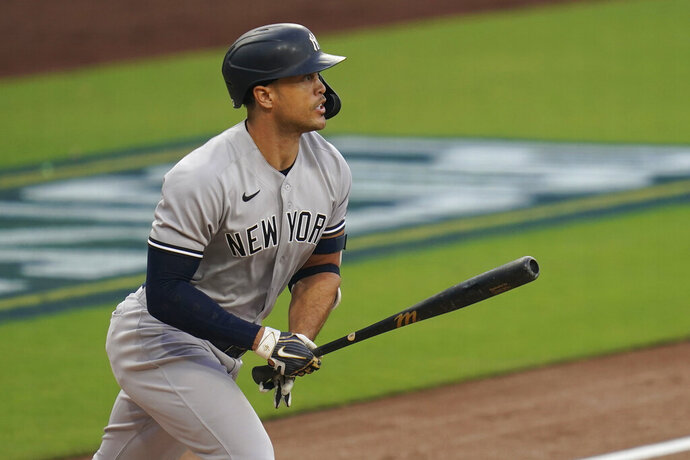 New York Yankees' Giancarlo Stanton watches his solo home run against the Tampa Bay Rays during the second inning in Game 2 of a baseball American League Division Series Tuesday, Oct. 6, 2020, in San Diego. (AP Photo/Gregory Bull)