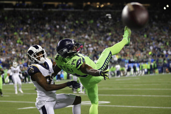 Seattle Seahawks wide receiver DK Metcalf, right, goes down next to Los Angeles Rams cornerback Marcus Peters as a pass for a 2-point conversion falls incomplete during the second half of an NFL football game Thursday, Oct. 3, 2019, in Seattle. (AP Photo/Stephen Brashear)