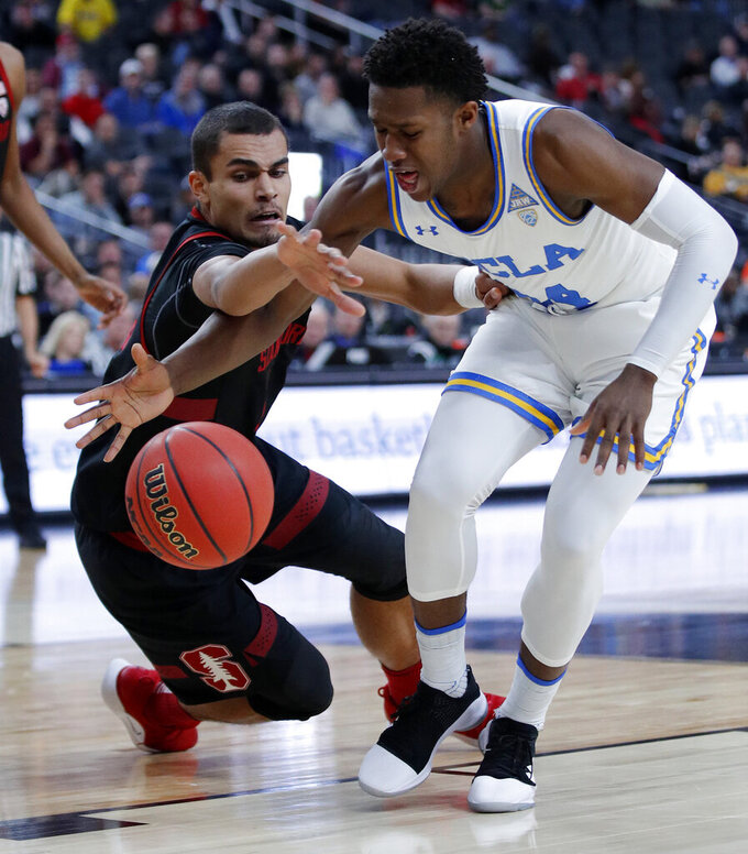 Stanford's Oscar Da Silva, left, and UCLA's David Singleton scramble for the ball during the first half of an NCAA college basketball game in the first round of the Pac-12 men's tournament, Wednesday, March 13, 2019, in Las Vegas. (AP Photo/John Locher)