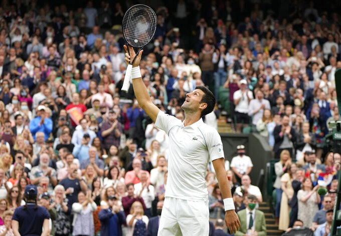 Serbia's Novak Djokovic celebrates winning the first round men's singles match against Britain's Jack Draper on day one of the Wimbledon Tennis Championships in London, Monday June 28, 2021. (AP Photo/Kirsty Wigglesworth)