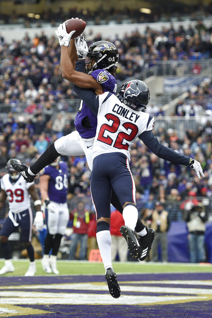 Baltimore Ravens wide receiver Seth Roberts, left, catches a touchdown pass from quarterback Lamar Jackson, not visible, as Houston Texans cornerback Gareon Conley (22) defends during the first half of an NFL football game, Sunday, Nov. 17, 2019, in Baltimore. (AP Photo/Gail Burton)
