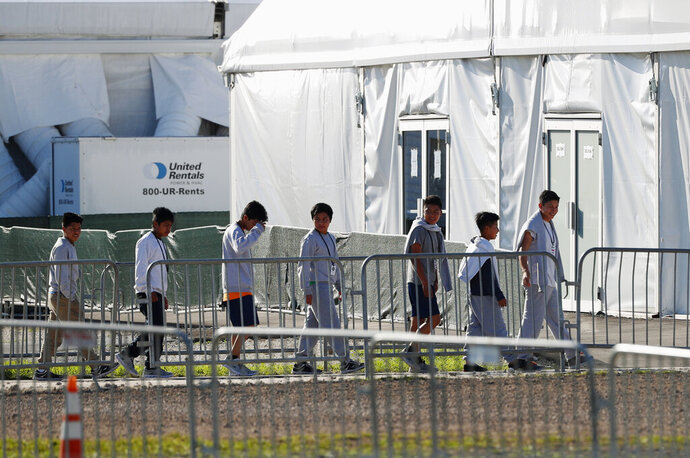 FILE - In this Feb. 19, 2019 file photo, youngsters line up to enter a tent at the Homestead Temporary Shelter for Unaccompanied Children in Homestead, Fla. Advocates for immigrant children are suing to block the Trump administration from enforcing a new policy that they say would erode legal protections for thousands of unaccompanied children seeking asylum in the U.S. (AP Photo/Wilfredo Lee, File)