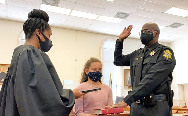 Circuit Judge Clyburn Pope administers the oath of office to Bamberg County Sheriff Kenny Bamberg, the rural South Carolina county's first Black sheriff,  as his granddaughter Aubree Bamberg holds the Bible on Tuesday, Jan. 5, 2021, at the Bamberg County Courthouse in Bamberg, S.C. (Martha Rose Brown/The Times and Democrat via AP)